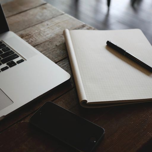 Photo of blank notepad and pen, smartphone and laptop - business coaching with Tracy Dempsey